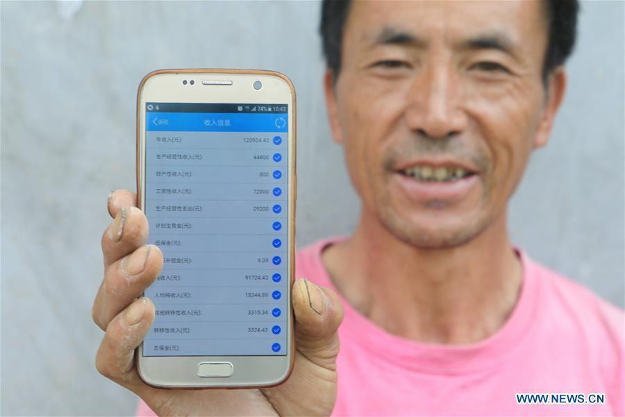 Wang Qingyou shows his family income using a mobile phone app in Guiyang, capital of southwest China\'s Guizhou Province, July 14, 2018. Guizhou has become a pioneer in China\'s big data development. Big data is being widely applied in government management, business and daily life, contributing over 20 percent to the economic growth of Guizhou Province. The number of big data-related companies in Guizhou Province has grown from less than 1,000 in 2013 to more than 8,500 in 2018.(Xinhua/Ou Dongqu)