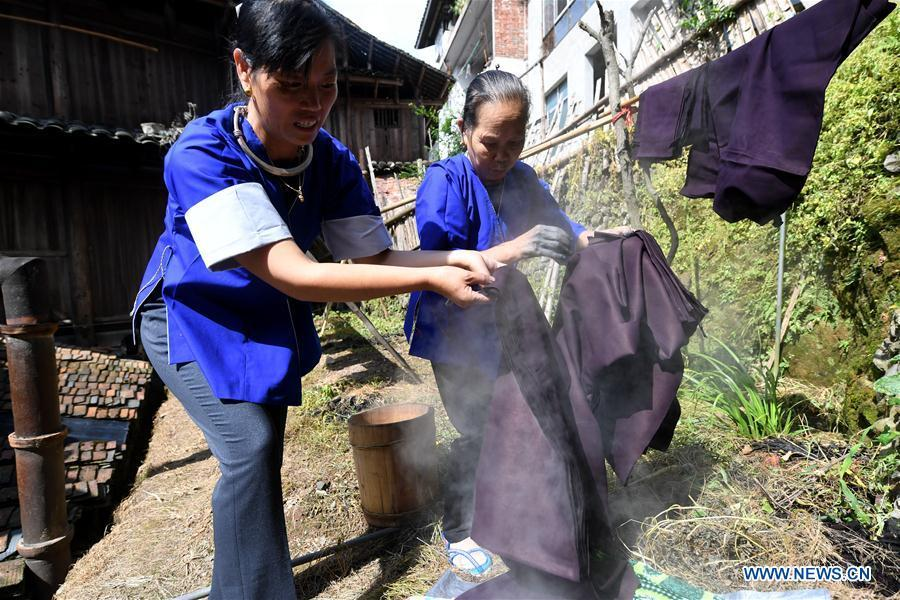 Women of the Dong ethnic group dry Dong cloth at Linxi Village of Sanjiang Dong Autonomous County under Liuzhou City, south China\'s Guangxi Zhuang Autonomous Region, Aug. 4, 2018. Summer is the best season for the people of the Dong ethnic group to make their traditional Dong cloth in ancient ways with natural materials. It is popular among the Dong people for its shining look in the sun and cozy quality for wearing. (Xinhua/Li Hanchi)