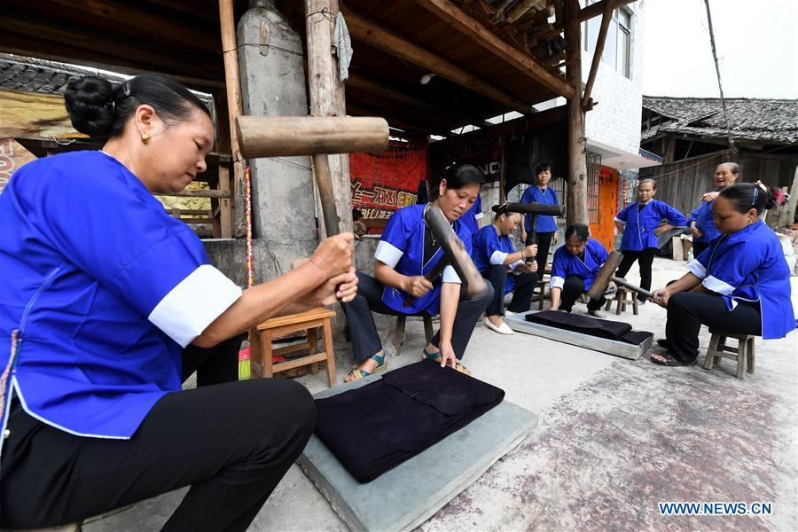 Women of the Dong ethnic group beat Dong cloth at Linxi Village of Sanjiang Dong Autonomous County under Liuzhou City, south China\'s Guangxi Zhuang Autonomous Region, Aug. 4, 2018. Summer is the best season for the people of the Dong ethnic group to make their traditional Dong cloth in ancient ways with natural materials. It is popular among the Dong people for its shining look in the sun and cozy quality for wearing. (Xinhua/Li Hanchi)
