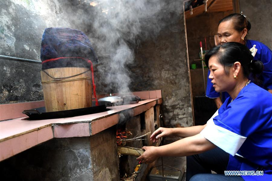 Women of the Dong ethnic group steam dyed Dong cloth at Linxi Village of Sanjiang Dong Autonomous County under Liuzhou City, south China\'s Guangxi Zhuang Autonomous Region, Aug. 4, 2018. Summer is the best season for the people of the Dong ethnic group to make their traditional Dong cloth in ancient ways with natural materials. It is popular among the Dong people for its shining look in the sun and cozy quality for wearing. (Xinhua/Li Hanchi)