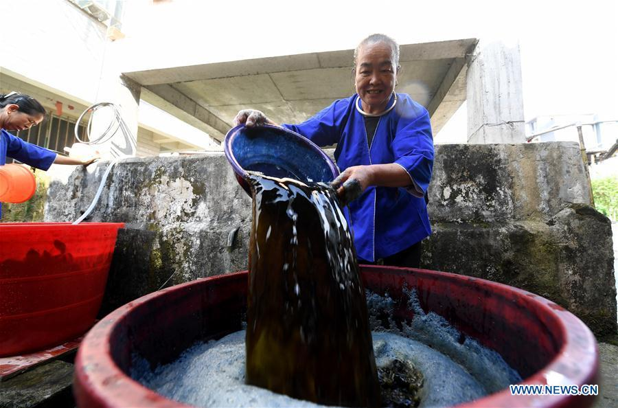 A woman of the Dong ethnic group makes dyeing material for Dong cloth at Linxi Village of Sanjiang Dong Autonomous County under Liuzhou City, south China\'s Guangxi Zhuang Autonomous Region, Aug. 4, 2018. Summer is the best season for the people of the Dong ethnic group to make their traditional Dong cloth in ancient ways with natural materials. It is popular among the Dong people for its shining look in the sun and cozy quality for wearing. (Xinhua/Li Hanchi)