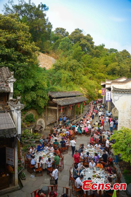 Nearly 1,000 visitors enjoy a long banquet along a street in the ancient Huangling village in Wuyuan, East China's Jiangxi Province, Aug. 4, 2018. The connected tables stretched for hundreds of meters, and local dishes were served up for tourists. (Photo: China News Service/Fang Huabinb)