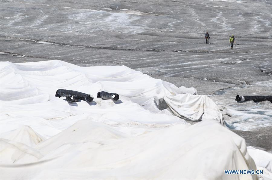 Hikers walk by the Rhone Glacier covered with white blankets near the Furka Pass in Switzerland, Aug. 5, 2018. The Rhone Glacier is protected by special white blankets to prevent it from further melting as a result of global warming. (Xinhua/Xu Jinquan)
