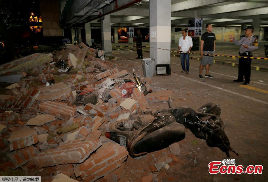 A policeman examines debris that fell and crushed parked motorbikes following a strong earthquake on nearby Lombok island, at a shopping center in Kuta, Bali, Indonesia  August 5, 2018. (Photo/Agencies)
