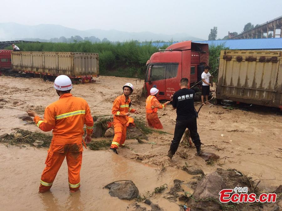 Rescuers help a driver escape from a truck trapped by mountain torrents in Fudian Town, Yanshi City, Central China's Henan Province, Aug. 5, 2018. Fifteen drivers were saved after a flash flood caused by a two-hour rainstorm trapped 50 trucks. (Photo/VCG)