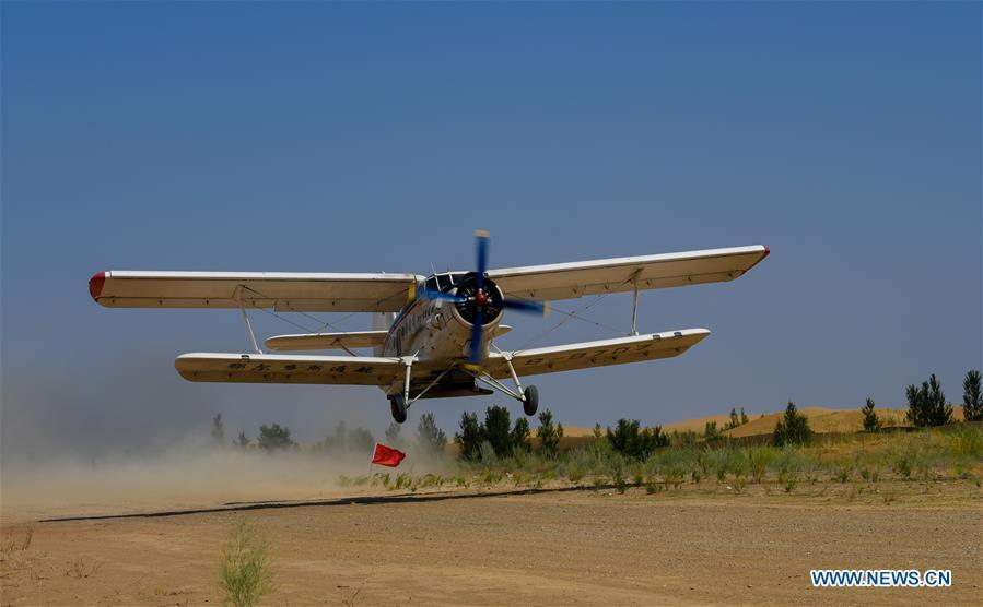 A plane takes off to sow seeds at the Kubuqi Desert in Erdos, north China\'s Inner Mongolia Autonomous Region, July 11, 2018. Kubuqi, the seventh largest desert in China, is a good example of China\'s success in alleviating desertification. About 6,460 square kilometers of the Kubuqi desert has been reclaimed in the last 30 years. (Xinhua/Peng Yuan)