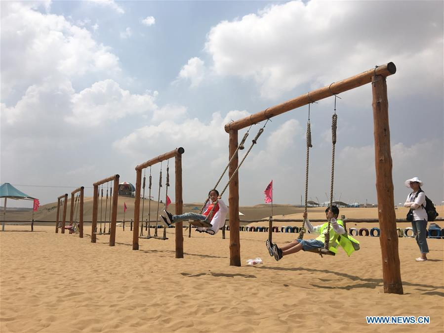 Tourists have fun at a scenic spot at the Kubuqi Desert in Erdos, north China\'s Inner Mongolia Autonomous Region, July 31, 2018. Kubuqi, the seventh largest desert in China, is a good example of China\'s success in alleviating desertification. About 6,460 square kilometers of the Kubuqi desert has been reclaimed in the last 30 years. (Xinhua/Zhang Shanchen)