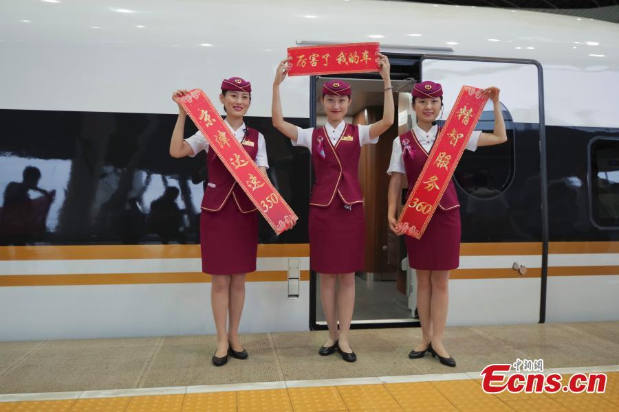 Attendants celebrate the start of Fuxing train running along the Beijing-Tianjin intercity high-speed railway at 350 kilometers per hour, up from 300 km/h, on Aug. 8, 2018. The Beijing-Tianjin intercity high-speed railway, one of China\'s calling cards, opened in August 2008. In 10 years, it has carried 250 million passengers. The new bullet train cuts the travel time between two cities from 35 minutes to 30 minutes. (Photo: China News Service/Jia Tianyong)