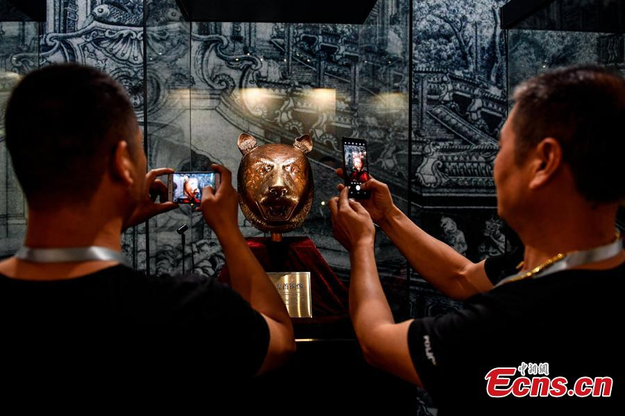 Visitors take photos at an exhibition displaying four original relics looted from Beijing\'s Old Summer Palace in 1860s underway in Zhaoqing City, Guangdong Province, Aug. 8, 2018. The four works are animal heads symbolizing the 12 animal signs of the Chinese zodiac, including pig, ox, monkey and tiger, which were originally water outlets, part of the fountain in the Old Summer Palace. Poly became a household name by acquiring the four animal heads from foreign auction houses, the centerpiece in Poly Art Museum in Beijing. (Photo: China News Service/Zhao Jimin)