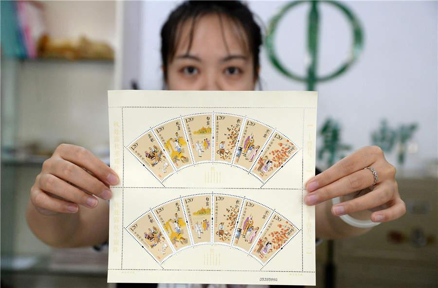 A staff member from the Handan branch of China Post shows the newly issued stamps featuring six solar terms in the autumn. (Photo/Asianewsphoto)