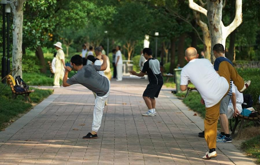 People practice Tai Chi in the park.