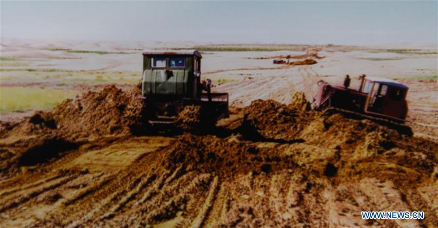 File photo shows people building a road at the Kubuqi Desert in 1990s, in Hangjin Banner, north China\'s Inner Mongolia Autonomous Region. Kubuqi, the seventh largest desert in China, is a good example of China\'s success in alleviating desertification. About 6,460 square kilometers of the Kubuqi desert has been reclaimed in the last 30 years. (Xinhua)
