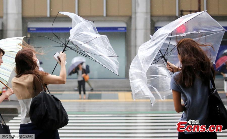 Passersby using umbrellas struggle against a heavy rain and wind as Typhoon Shanshan approaches Japan\'s mainland in Tokyo, Japan, Aug. 8, 2018. (Photo/Agencies)