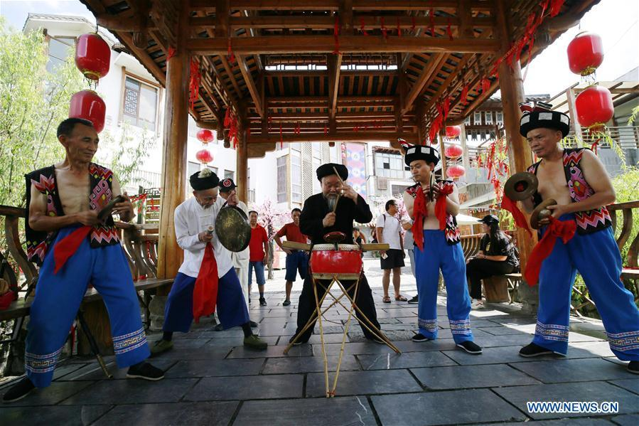 Jin De\'an (2nd L) and his team perform Daliuzi at Xibu Street, a scenic spot in the Wulingyuan District of Zhangjiajie City, central China\'s Hunan Province, Aug. 7, 2018. Daliuzi is a kind of local musical instrument performance with a long history. Jin De\'an is the creator of \