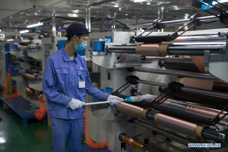 A staff member works on a production line of copper foil for making lithium battery at Huachuang New Material Co., Ltd in Tongling City, east China\'s Anhui Province, Aug. 8, 2018. Tongling government takes measures to improve ecological environment and develop green industry along the Yangtze River. (Xinhua/Jin Liwang)