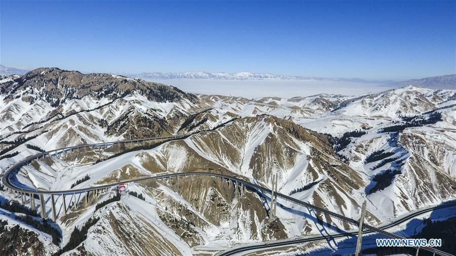 Aerial photo taken on Jan. 26, 2018 shows the Lianyungang-Horgos expressway along the Tianshan Mountains, northwest China\'s Xinjiang Uygur Autonomous Region. As an important link of the Silk Road Economic Belt, Xinjiang is speeding up the development of transportation and logistics to connect east and west. By the end of 2017, the total length of roads in Xinjiang reached 186,000 km, with 4,578 km of expressways. (Xinhua/Hu Huhu)