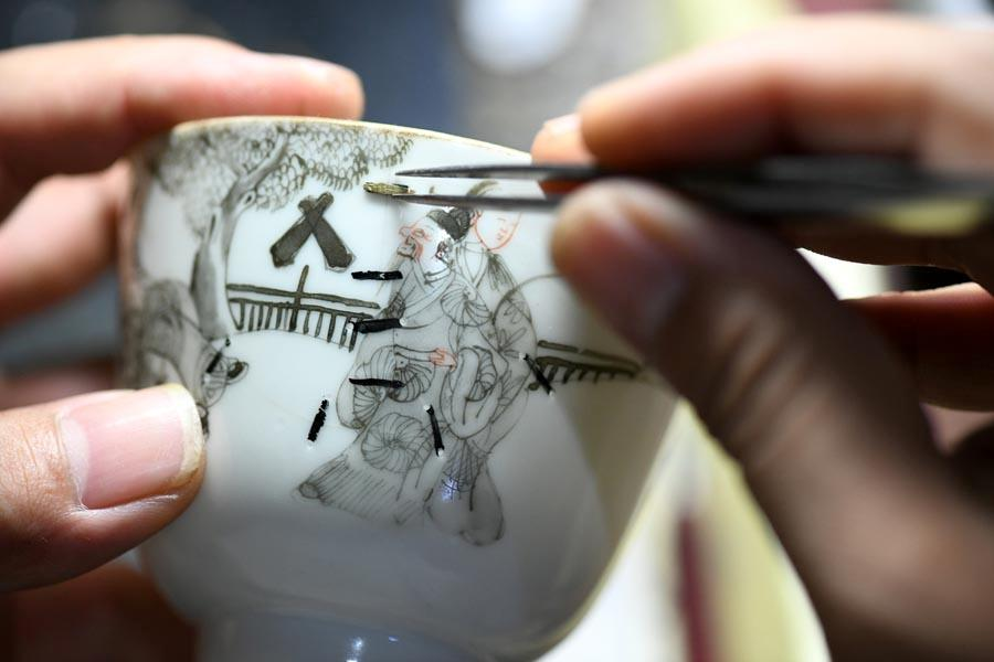 Li Junhang, a Hebei-based inheritor of the old craft of juci, or porcelain restoration, embeds a nail into a broken porcelain ware to make it complete. Over the past two decades, Li has infused Chinese calligraphy and painting into the ancient repair skill, adding artistic flairs to broken ceramic wares. (Photo/Xinhua)