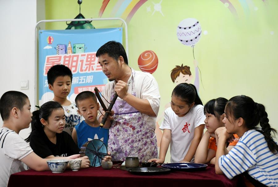 Li Junhang teaches local students the craftsmanship of porcelain restoration in Shijiazhuang, Hebei Province, Aug. 8, 2018.  (Photo/Xinhua)