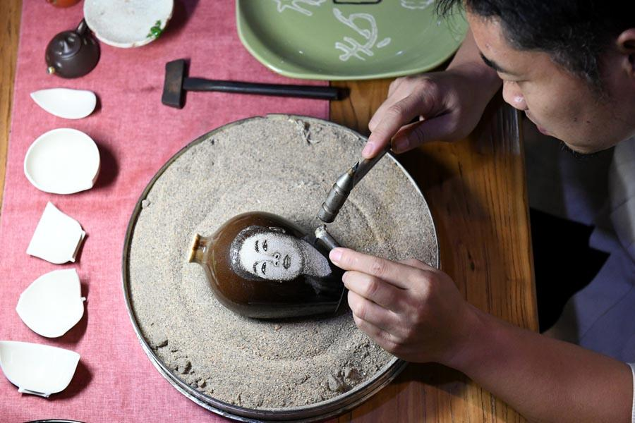 Li Junhang creates a portrait on a porcelain piece on Aug., 6, 2018. (Photo/Xinhua)