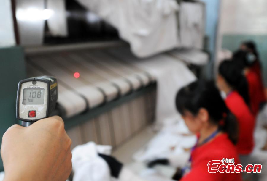 Workers clean bedding for sleeper carriages on trains in Jiujiang City, East China's Jiangxi Province, Aug. 8, 2018. During the summer travel peak, laundry service workers have to clean up to 20,000 sets of linen a day, double their normal workload, despite the high temperatures at 50 degrees centigrade. (Photo: China News Service/Hu Guolin)