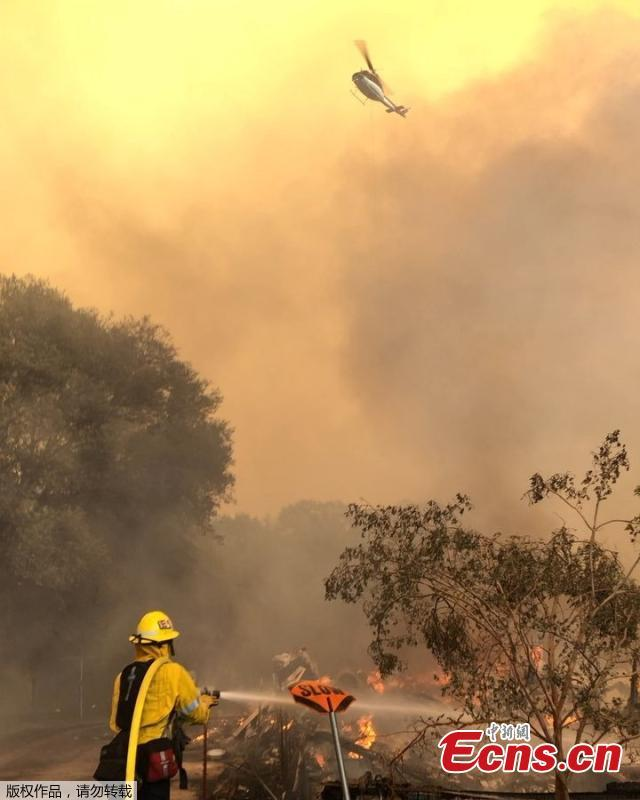 Firefighters battle wildfires as a helicopter hovers above an area near Mendocino National Forest, California, the U.S. August 4,  2018 in this picture obtained from social media. (Photo/Agencies)