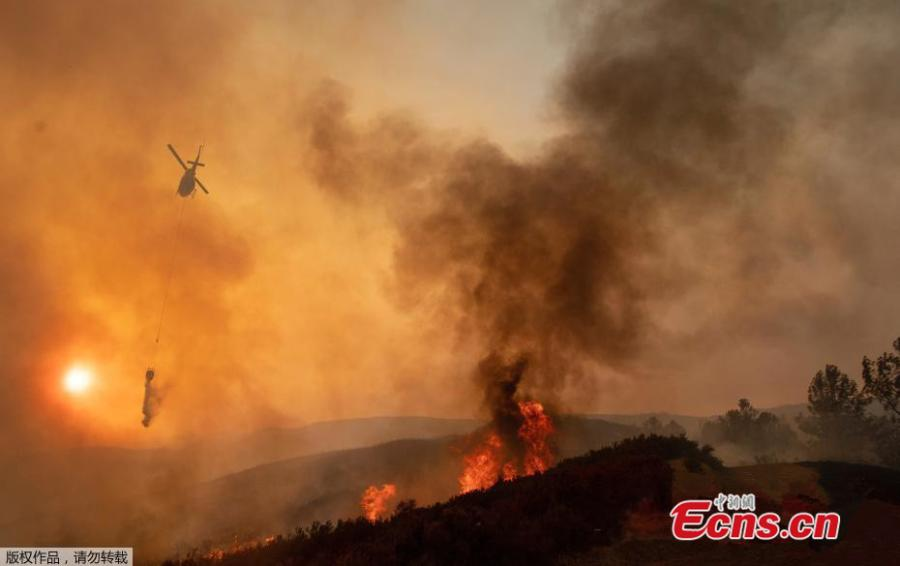 Firefighters battle wildfires as a helicopter hovers above an area near Mendocino National Forest, California, the U.S., Aug. 4, 2018 in this image obtained from social media. (Photo/Agencies)