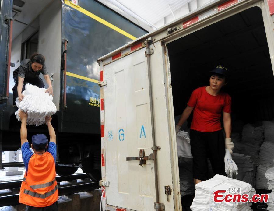 Railway workers transport clean bed linen destined for sleeper carriages on trains in Jiujiang City, East China's Jiangxi Province, Aug. 8, 2018. During the summer travel peak, laundry service workers have to clean up to 20,000 sets of linen a day, double their normal workload, despite the high temperatures at 50 degrees centigrade. (Photo: China News Service/Hu Guolin)