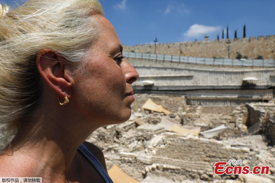 Professor Cayetana Johnson wears a rare golden earring believed to be more than 2,000 years-old, discovered at the archeological site of the City of David in East Jerusalem near the walls of the old city on 8 August 2018. A Hellenistic-era golden earring, featuring ornamentation of an horned animal, was discovered in the Givati Parking Lot in the City of David National Park encircling the Old City walls. The discovery was made during archeological digs carried out by the Antiquities Authority and Tel Aviv University. The spectacular gold earring, shaped like a horned animal, dates back to the second or third century BCE, during the Hellenistic period. (Photo/Agencies)