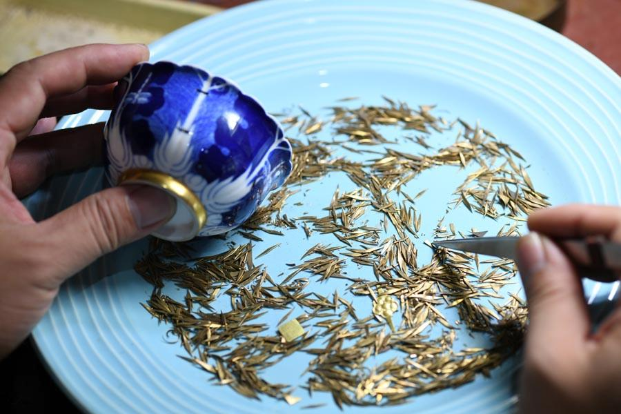 Li Junhang picks a suitable nail for a broken porcelain bowl, at his studio in North China\'s Hebei Province, Aug. 6, 2018.  (Photo/Xinhua)