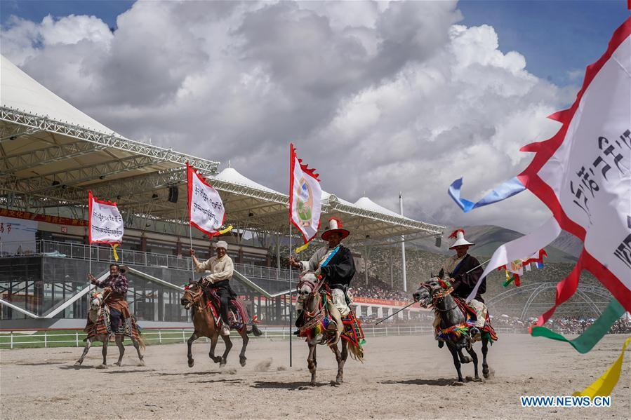 Riders enter the race course during the opening ceremony of a horse racing festival in Damxung County, southwest China\'s Tibet Autonomous Region, Aug. 8, 2018. Dangjiren horse racing is originated from military parade of Mongolian cavalry since 17th century. (Xinhua/Cen Yunpeng)