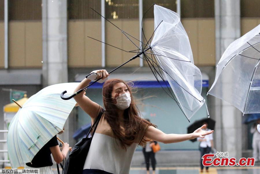 A woman using an umbrella struggles against a heavy rain and wind as Typhoon Shanshan approaches Japan\'s mainland in Tokyo, Japan, Aug. 8, 2018. (Photo/Agencies)