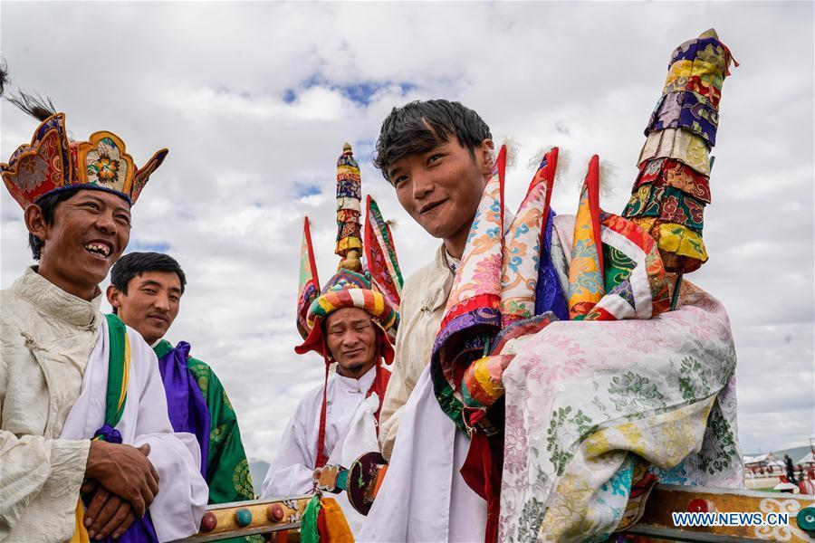 A herdsman(R) introduces his costume before the opening ceremony of a horse racing festival in Damxung County, southwest China\'s Tibet Autonomous Region, Aug. 8, 2018. Dangjiren horse racing is originated from military parade of Mongolian cavalry since 17th century. (Xinhua/Cen Yunpeng)