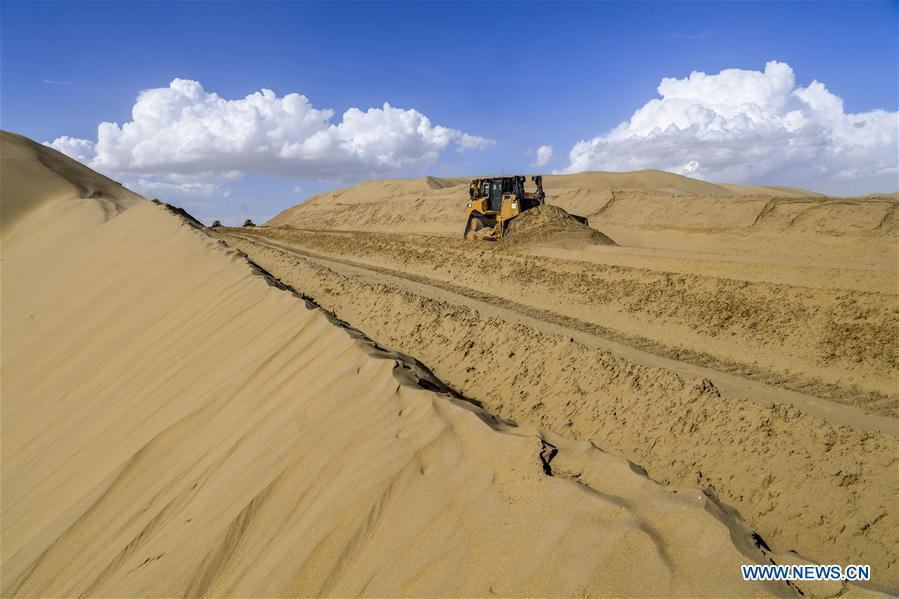 Photo taken on July 5, 2018 shows the construction site of the desert road linking Yuli County to Qiemo County in northwest China\'s Xinjiang Uygur Autonomous Region. As an important link of the Silk Road Economic Belt, Xinjiang is speeding up the development of transportation and logistics to connect east and west. By the end of 2017, the total length of roads in Xinjiang reached 186,000 km, with 4,578 km of expressways. (Xinhua/Hu Huhu)