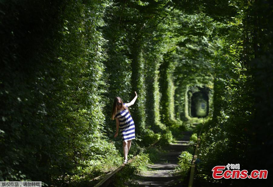 A girl walks along former railway tracks in the so-called \'Tunnel of Love\', surrounded by arches of intertwined trees, near the Ukrainian village of Klevan, Rivno region, Aug. 6, 2018. The tunnel of about five kilometers in length is a botanical phenomenon, which became a cult place for tourists and couples in love. The tourist legend says that wishes of couples in love will come true, if the couple passes through the tunnel. (Photo/Agencies)