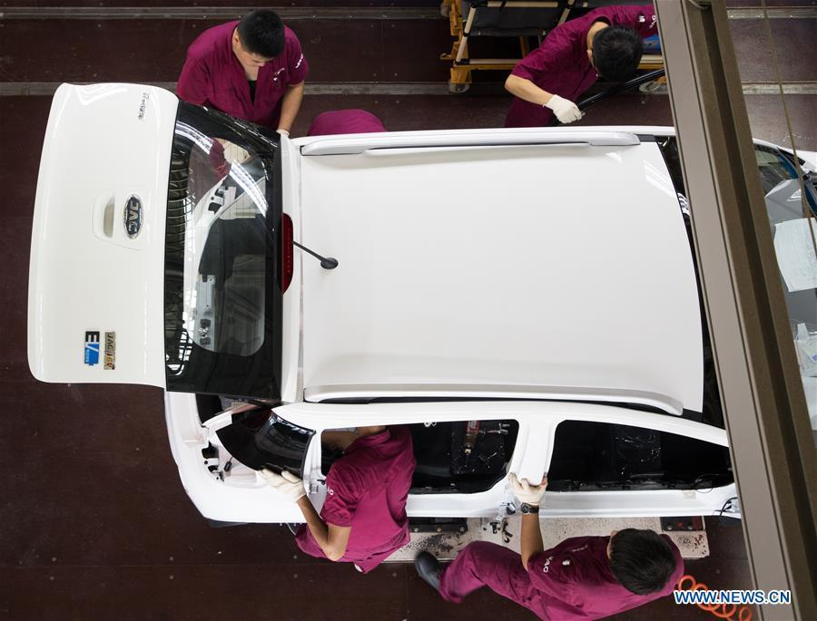 Staff members work on a new energy vehicle at a JAC Motors factory in Tongling City, east China\'s Anhui Province, Aug. 7, 2018. Tongling government takes measures to improve ecological environment and develop green industry along the Yangtze River. (Xinhua/Jin Liwang)