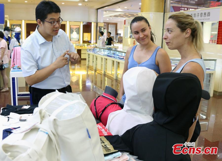 Customers buy souvenirs released by the Beijing Organizing Committee for the 2022 Olympic and Paralympic Winter Games to mark the 10thanniversary of Beijing's hosting of the 2008 Summer Olympics in the Gongmei Building in Wangfujing, Beijing, Aug. 8, 2018. (Photo: China News Service/Ren Haixia)