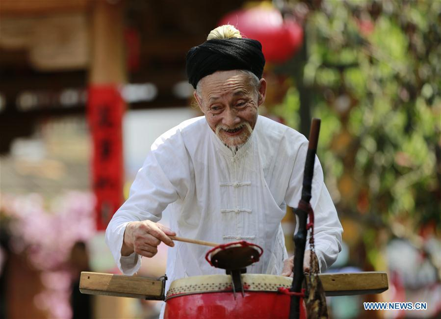 Jin De\'an performs Daliuzi at Xibu Street, a scenic spot in the Wulingyuan District of Zhangjiajie City, central China\'s Hunan Province, Aug. 7, 2018. Daliuzi is a kind of local musical instrument performance with a long history. Jin De\'an is the creator of \