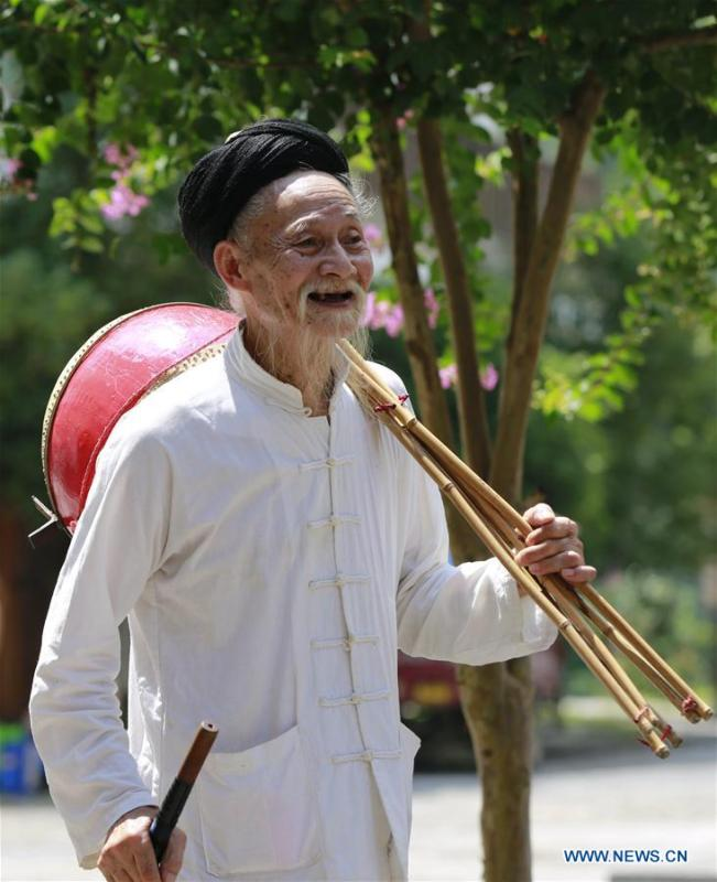 Jin De\'an prepares to perform Daliuzi at Xibu Street, a scenic spot in the Wulingyuan District of Zhangjiajie City, central China\'s Hunan Province, Aug. 7, 2018. Daliuzi is a kind of local musical instrument performance with a long history. Jin De\'an is the creator of \