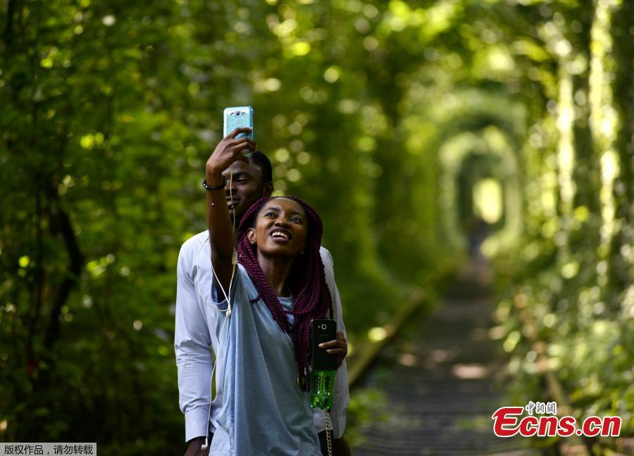 A couple takes selfies as they walk along former railway tracks surrounded by arches of intertwined trees in the so-called \'Tunnel of Love\', near the Ukrainian village of Klevan, Rivno region, Aug. 6, 2018. The tunnel of about five kilometers in length is a botanical phenomenon, which became a cult place for tourists and couples in love. The tourist legend says that wishes of couples in love will come true, if the couple passes through the tunnel. (Photo/Agencies)