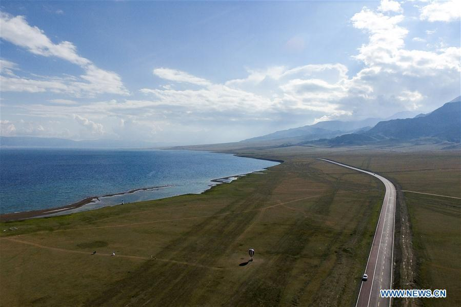 Aerial photo taken on July 5, 2018 shows the Lianyungang-Horgos expressway along the Sayram Lake, northwest China\'s Xinjiang Uygur Autonomous Region. As an important link of the Silk Road Economic Belt, Xinjiang is speeding up the development of transportation and logistics to connect east and west. By the end of 2017, the total length of roads in Xinjiang reached 186,000 km, with 4,578 km of expressways. (Xinhua/Zhao Ge)