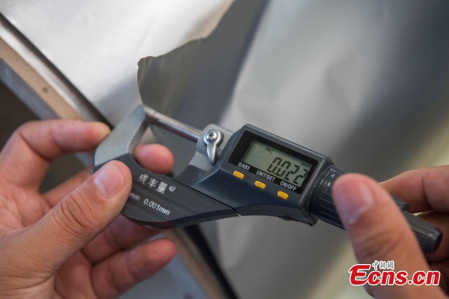 A worker shows stainless steel 0.02 millimeters thick at a company in Taiyuan City, the capital of North China's Shanxi Province, Aug. 8, 2018. The company started mass production of the advanced 0.02-millimeter-thick, 600-millimeter-wide stainless steel, which is said to have wide applications in a range of fields, including aerospace, automotive, electronics and computers. Sources said due to difficult production techniques, China used to import the product from Japan and Germany. (Photo: China News Service/Wei Liang)