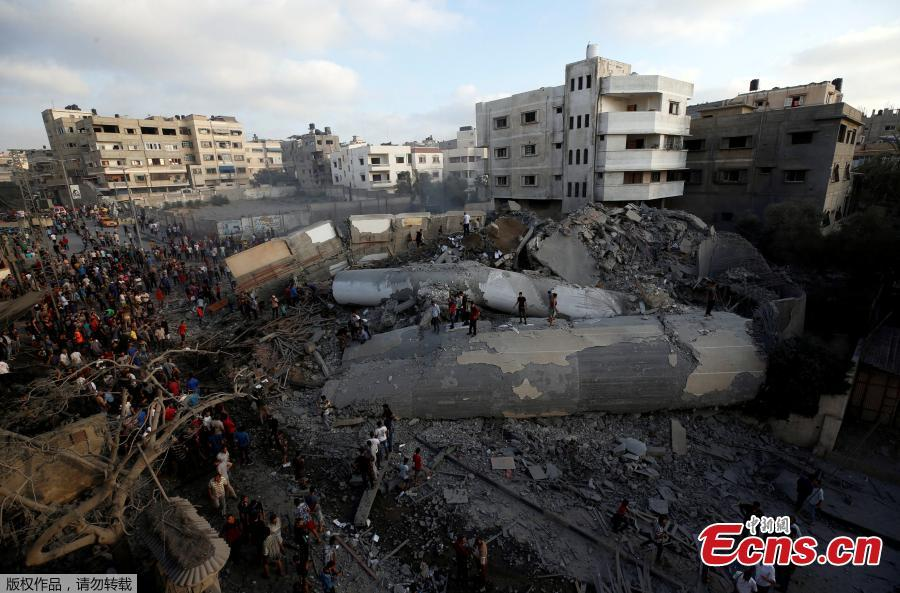 Palestinians gather around a building after it was bombed by an Israeli aircraft, in Gaza City, August 9, 2018. On Wednesday night and Thursday, Israeli aircraft struck more than 150 targets in Gaza and Palestinian militants fired scores of rockets including a long-range missile deep into Israel, escalating fighting despite the ongoing truce talks. (Photo/Agencies)