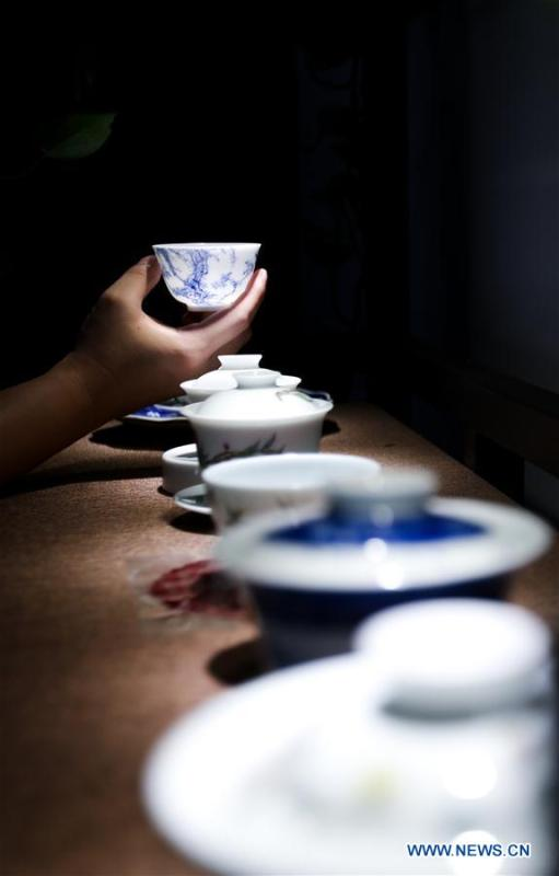 A visitor watches a tea cup made by the \