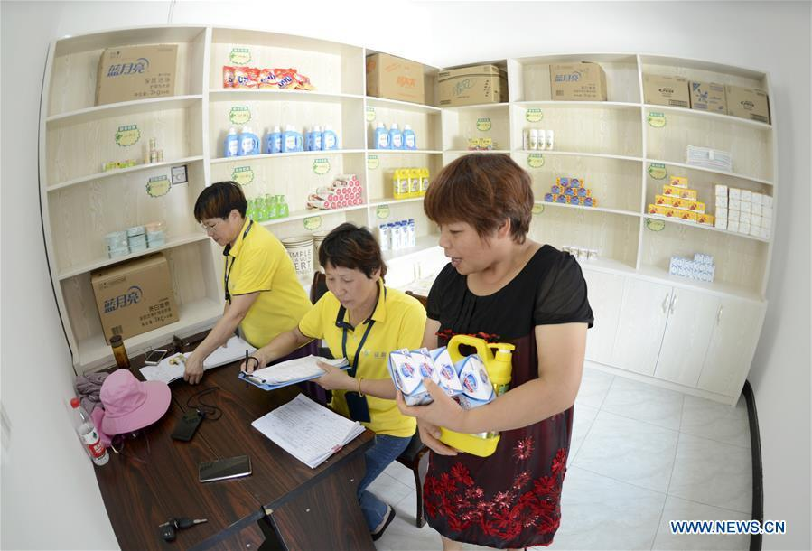 A villager redeems commodities in a supermarket using points earned through garbage classification in Lipu Township of Zhuji City, east China\'s Zhejiang Province, Aug. 9, 2018. Local government has rolled out a mechanism to encourage people to do garbage sorting, in which residents can redeem commodities with points earned from garbage classification or by answering questions about garbage classification. (Xinhua/Han Chuanhao)