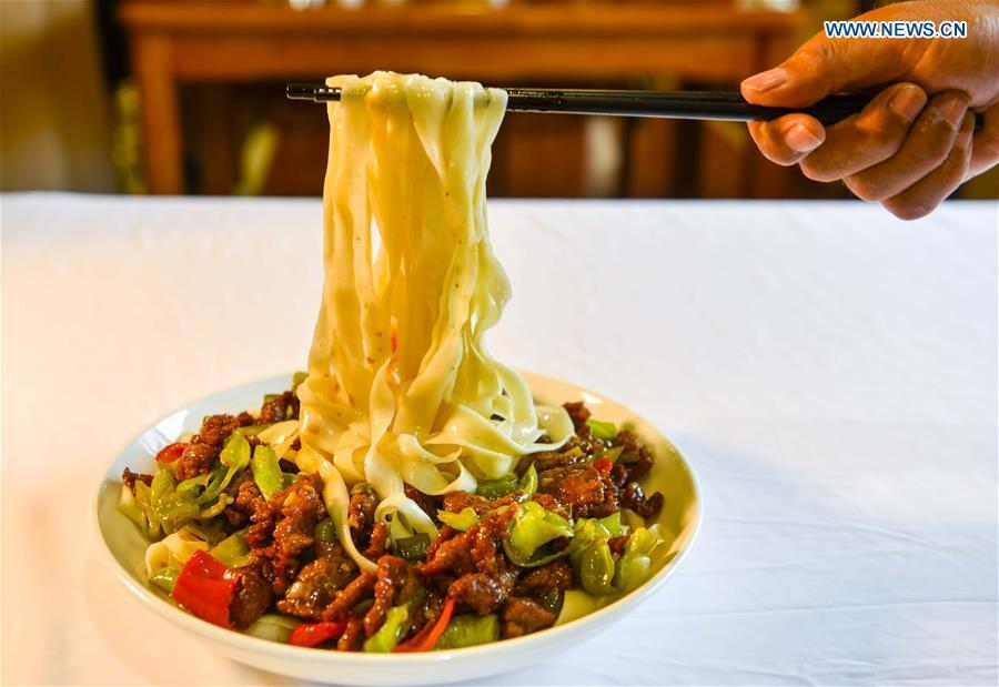 A cook shows a local dish of noodles at a restaurant in Qitai, northwest China\'s Xinjiang Uygur Autonomous Region, July 25, 2018. (Xinhua/Wang Fei)