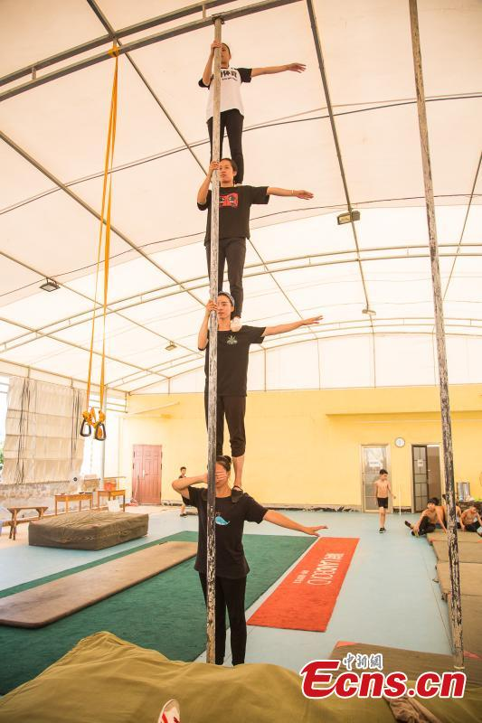 Acrobat Li Xianhui, 22, trains with other members at a gym in Nanning, the capital of South China's Guangxi Zhuang Autonomous Region, Aug. 9, 2018. Most of the children training with the acrobatics troupe led by Li Dewei are from the poverty-stricken Mashan County and they dream of one day improving the financial position of their families through their performances. A member of the acrobatics troupe for ten years, Li has performed in many countries. (Photo: China News Service/Chen Guanyan)