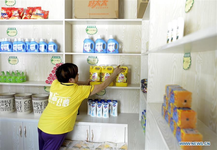 A staff member arranges commodities exchangeable in a supermarket for points earned through garbage classification in Lipu Township of Zhuji City, east China\'s Zhejiang Province, Aug. 9, 2018. Local government has rolled out a mechanism to encourage people to do garbage sorting, in which residents can redeem commodities with points earned from garbage classification or by answering questions about garbage classification. (Xinhua/Han Chuanhao)