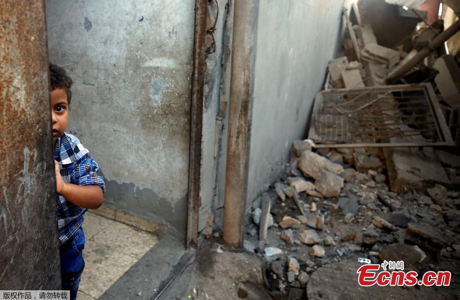 A Palestinian boy looks out of his family\'s house that was damaged in an Israeli air strike, in Al-Mughraqa on the outskirts of Gaza City, August 9, 2018. On Wednesday night and Thursday, Israeli aircraft struck more than 150 targets in Gaza and Palestinian militants fired scores of rockets including a long-range missile deep into Israel, escalating fighting despite the ongoing truce talks. (Photo/Agencies)