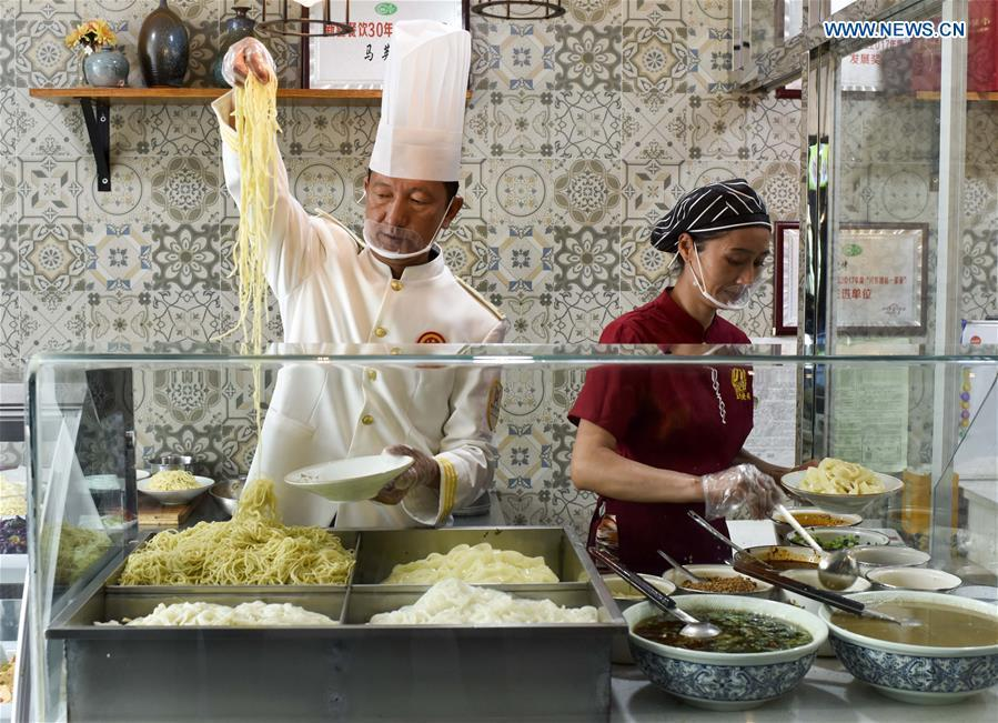 Cooks make cold noodles at a restaurant in Qitai County, northwest China\'s Xinjiang Uygur Autonomous Region, July 25, 2018. (Xinhua/Zhao Ge)
