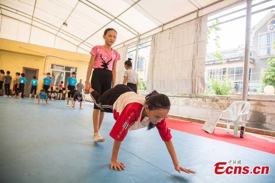 Twin sisters Wei Liufei (L) and Wei Meifei, 12, train at a gym in Nanning, the capital of South China's Guangxi Zhuang Autonomous Region, Aug. 9, 2018. Most of the children training with the acrobatics troupe led by Li Dewei are from the poverty-stricken Mashan County and they dream of one day improving the financial position of their families through their performances. (Photo: China News Service/Chen Guanyan)